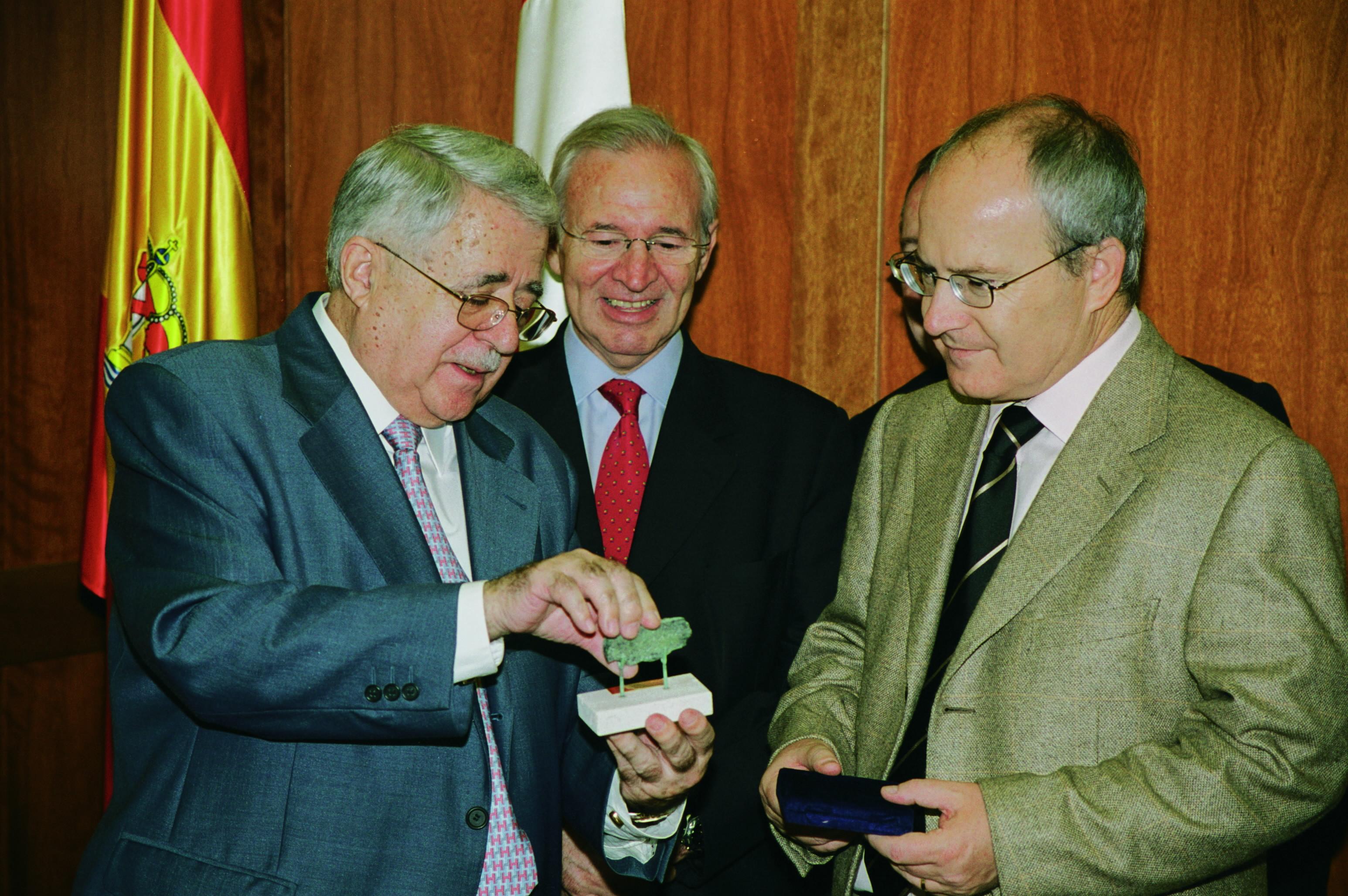 """Jesús Mora Mas entrega a José Montilla, Presidente de la Generalitat la """"Tessera Hospitalis"""", símbolo utilizado en la exposición «100 AÑOS DE HOSPITALIDAD, UN SIGLO DE HOSTELERÍA Y SOCIEDAD» presentada en HOSTELCO 2004 como punto de partida de lo que ha sido, es y será la característica fundamental de los que abren sus brazos para la dar la bienvenida a los que les visitan"""
