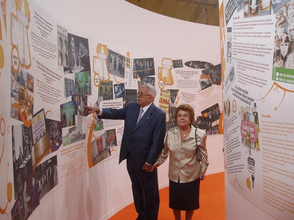 Jesús Mora Mas con María visitando la Exposición «HOSTELCO: 25 AÑOS HACIENDO HISTORIA» en HOSTELCO 2006