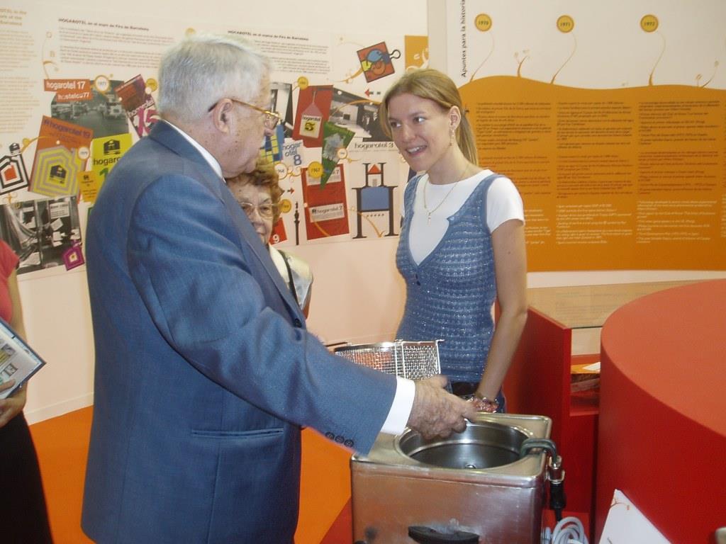 Jesús Mora Mas junto a María explica a los visitantes sobre diferentes aspectos de la maquinaria presentada en la exposición «HOSTELCO: 25 AÑOS HACIENDO HISTORIA» presentada en HOSTELCO 2006
